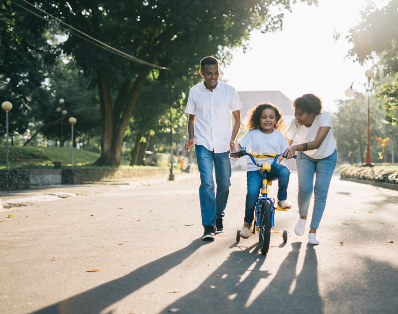 Mother and Father help young child learn to ride a bike